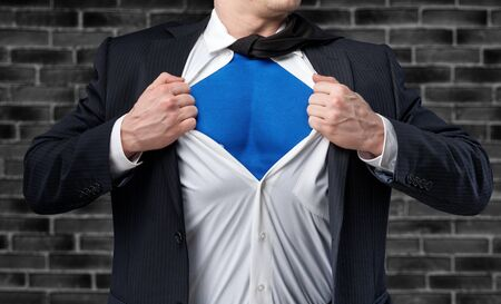 Businessman tears shirt on himself to show that he is Superhero isolated on white background