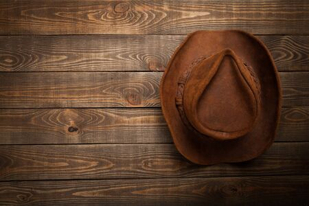American West rodeo country farmer traditional straw hat hanging on distressed wood boards wall in a vintage ranch barn