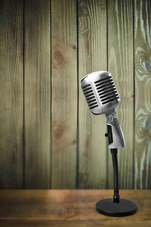 Retro microphone on wood background