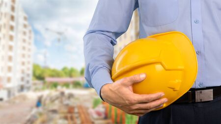 Close-up shot of a foreman holding a hardhat on the construction site Stockfoto
