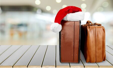 Retro large suitcases with Santa hat Фото со стока