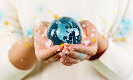 Vrouwelijke handen met glazen bol op de achtergrond Stockfoto