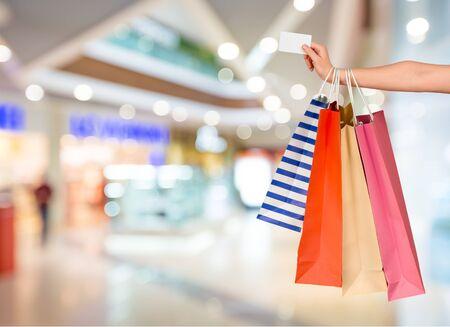 Chiuda sulla mano della donna con molti sacchetti della spesa e carta di credito