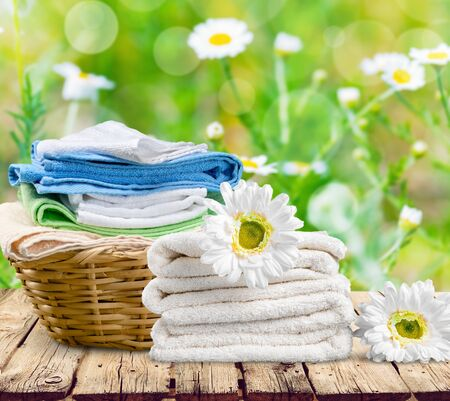 Laundry Basket with colorful towels on background Standard-Bild - 129956012
