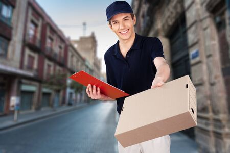 Smiling young man delivering box