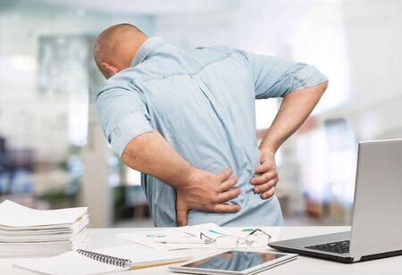 Bedrijfsmens met rugpijn een bureau