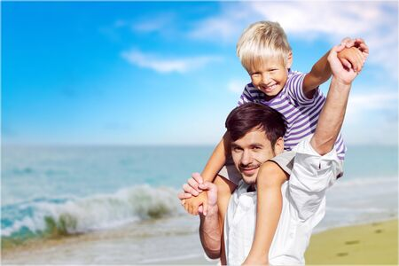 loving father with son on shoulders walking on the beach carefree and happy