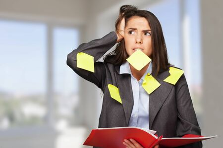 Businesswoman standing with copybook and sticky notes Stock fotó