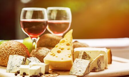 Assortment of cheese on board and two glasses of wine 写真素材
