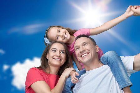 Happy cheerful young family on sky background Zdjęcie Seryjne