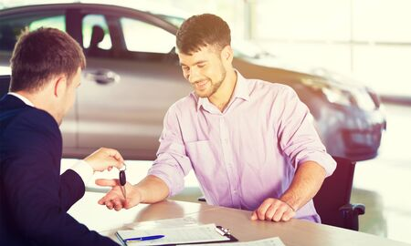 Happy man with car dealer in auto show