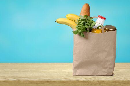 Full shopping  bag on wooden table Foto de archivo - 130159385