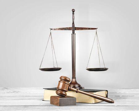 Gerechtigkeitswaagen und Buch und Holzhammer auf dem Tisch. Gerechtigkeitskonzept