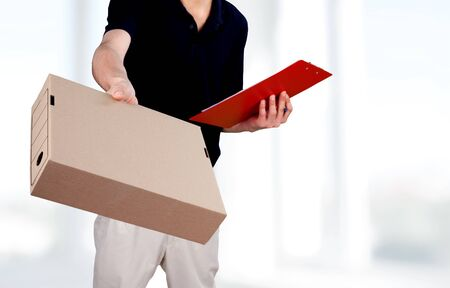 Man delivering package, holding clipboard for signature