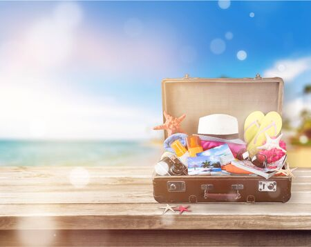 Retro suitcase with travel objects on wooden board on natural Stockfoto