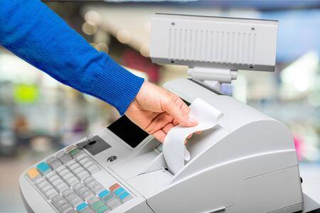 Registratore di cassa con display LCD e mano del lavoratore che tiene la carta della ricevuta sopra l'interno sfocato del supermercato Archivio Fotografico