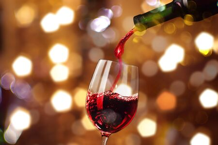 Red wine pouring in glass isolated bokeh