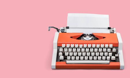 A typewriter on a pink table Foto de archivo