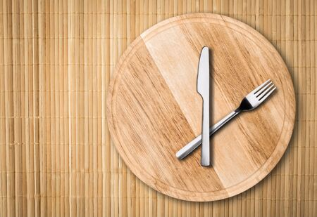 Wooden round tray or trencher with cutlery Stock Photo - 130155489