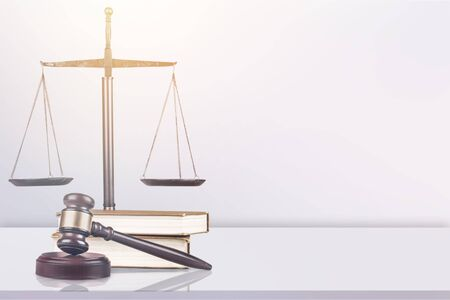 Justice Scales and books and wooden gavel on table.
