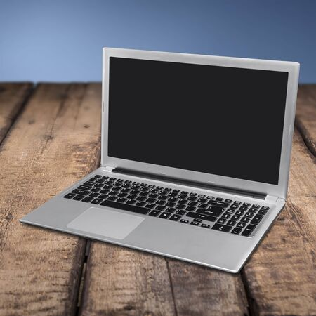Laptop isolated on wooden table Stock fotó