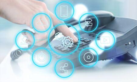 Chiudere il punto della mano dell'uomo del call center dei dipendenti per premere il numero del pulsante sulla scrivania dell'ufficio del telefono con il concetto di tecnologia di comunicazione virtuale
