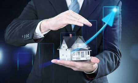 Businessman hand holding house representing home ownership and the Real Estate business with tablet. 스톡 콘텐츠