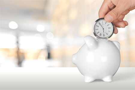 Hand depositing clock in piggy bank on white table