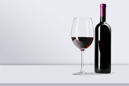 Red wine glass on wooden desk on white