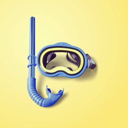 Diving mask and a snorkel on yellow