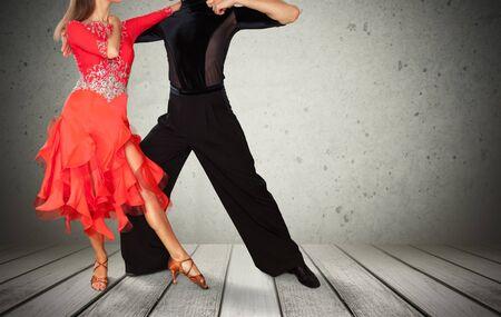 Man and a woman dancing Salsa on grey wall Фото со стока