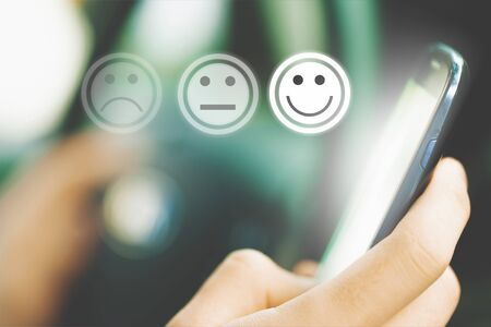 Businesswoman pressing face emoticon on virtual touch screen at smartphone .Customer service evaluation concept. - Image