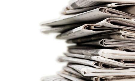 Pila de periódicos sobre fondo blanco.