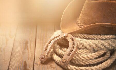 Old horseshoe , lariat lasso and cowboy hat on background Stock Photo