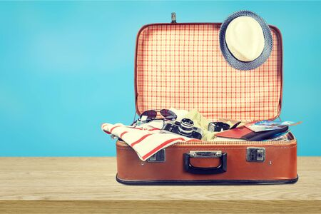 Retro suitcase with travel objects on light