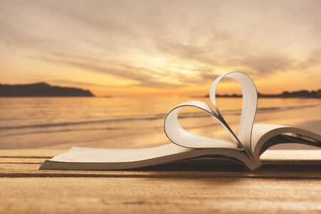 Heart shape from book against peaceful sunset. Reading, religion, love concept. Double exposure. 版權商用圖片