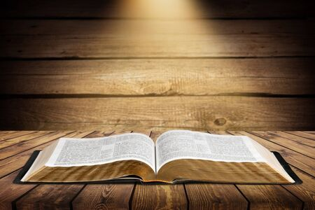 A beam of light falls on an old open sacred book on a wooden table