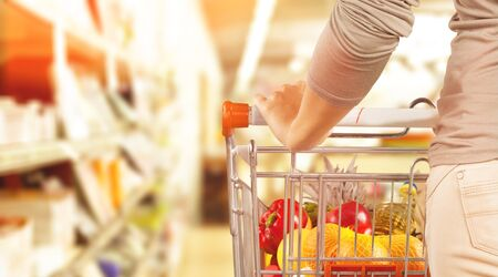 woman hand hold shopping cart with Abstract blur supermarket aisle defocused background