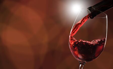 Red wine pouring in glass on background Foto de archivo