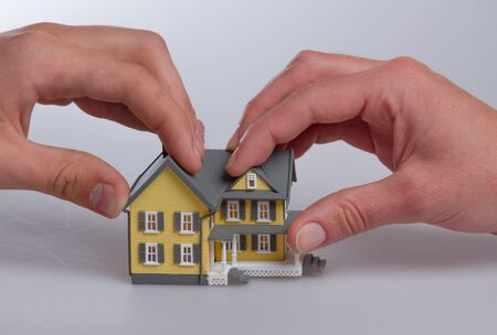Human Hands Holding a Model of a House on Grey Background