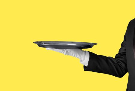 Elegant waiter hand in white glove holding an empty plate with blank gradient background.