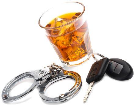 kieliszek trunku z kluczykami do samochodu i kajdankami