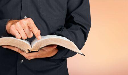 Man in black dress reading holy bible