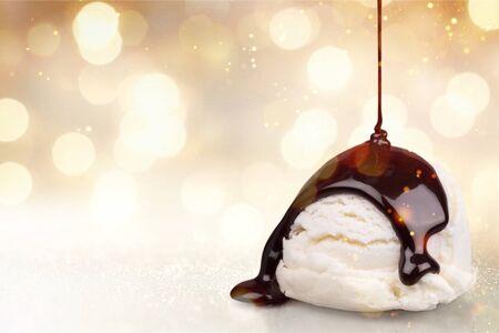 Vanilla ice cream with chocolate sauce on white background