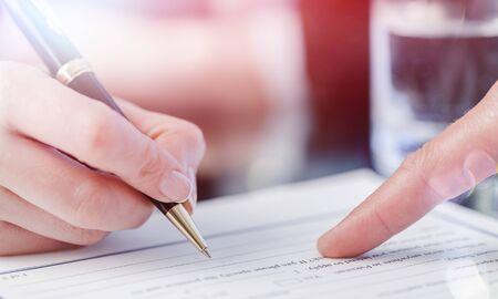 Männliche Hand zeigt auf eine Stelle, um ein Papier zu unterschreiben