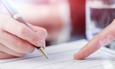 Mannenhand wijzend naar een plek om een papier te ondertekenen