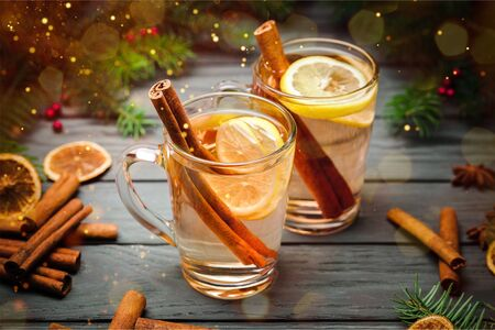 Mulled white wine with cinnamon in glasses on wooden background