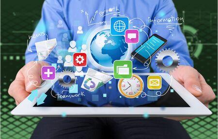 Empresario y tablet pc con iconos de negocios abstractos sobre fondo Foto de archivo
