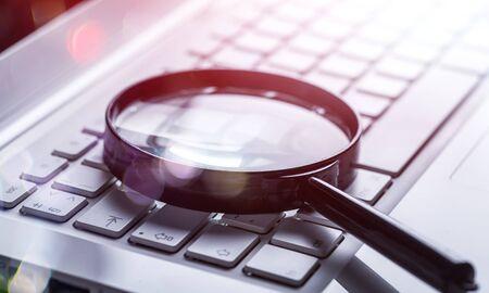 Vergrootglas op laptop toetsenbord close-up
