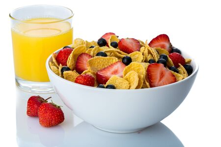Schüssel mit Cornflakes, Heidelbeeren, Erdbeeren und Orangensaft